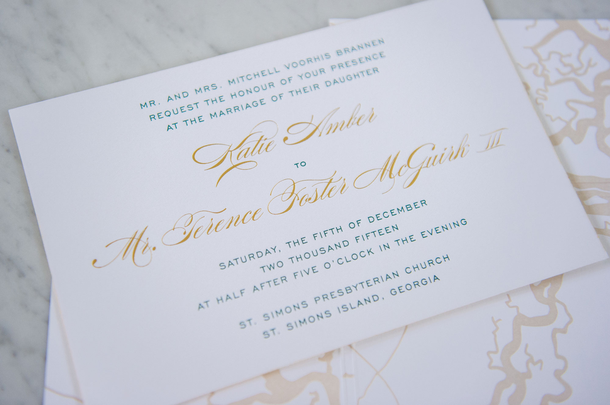 letterpress invitation suite, with green paper and glass-cloth wallpaper. letterpress map. gold foil  with full solid coverage. All displayed on a marble slab.