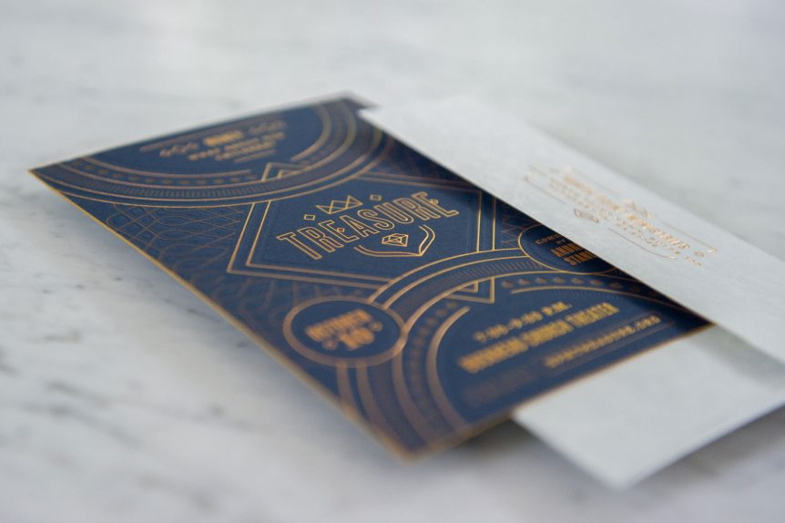 Blue letterpress invitation with copper foil stamp and copper ink press into paper displayed on marble