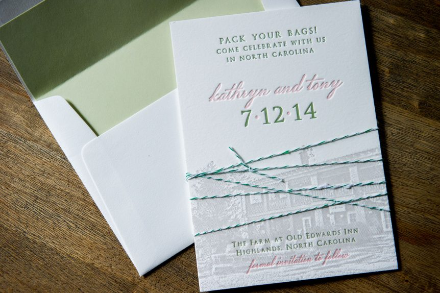 Letterpress save the date 3-piece announcement that is bound by green and white baker's twine. lined envelope, set on wood background