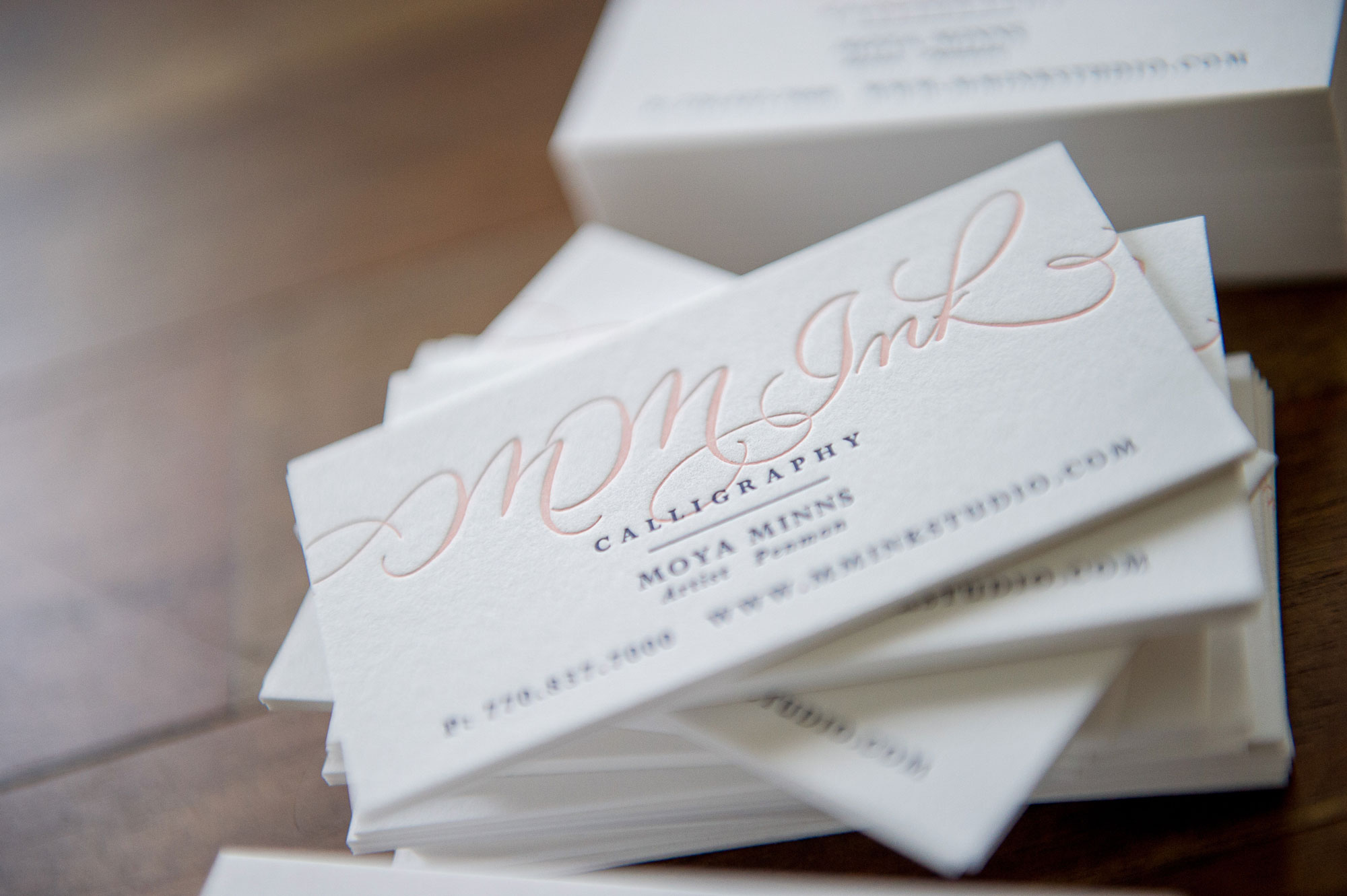 MM Ink Calligraphy, 2 color letterpress business card print on Crane Lettra 220# thick stock on a wooden background